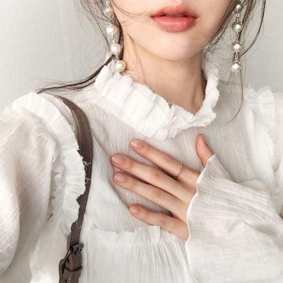Chica asiática con aretes grandes de perlas