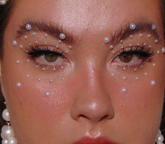 Mujer rubia con maquillaje luminoso y perlas