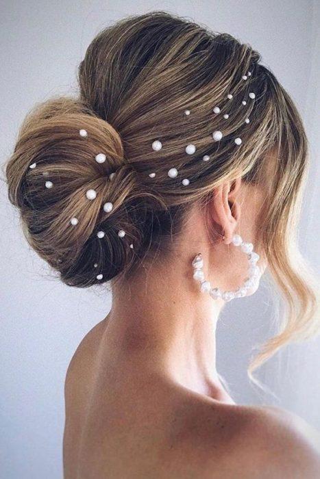 Mujer rubia con recogido bajo con perlas