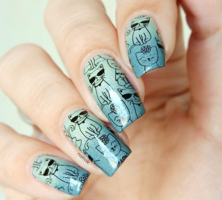 Mint color manicure with gradient effect and decorated with stickers of cats silhouettes
