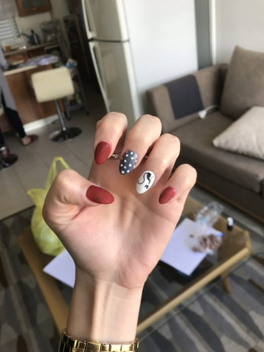 Manicure in shades of red, blanoc and black with decorated cats