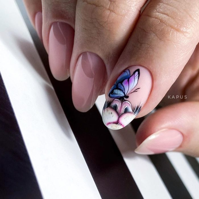 Almond-shaped manicure in pink and decorated with a butterfly in purple