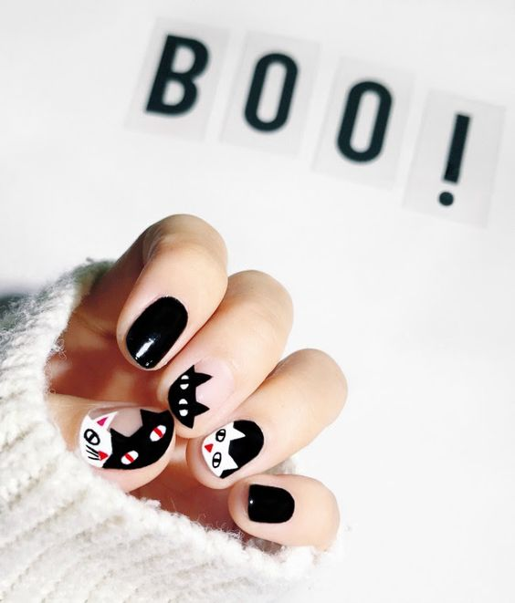 Manicure with black nails and decorated with cats in white color