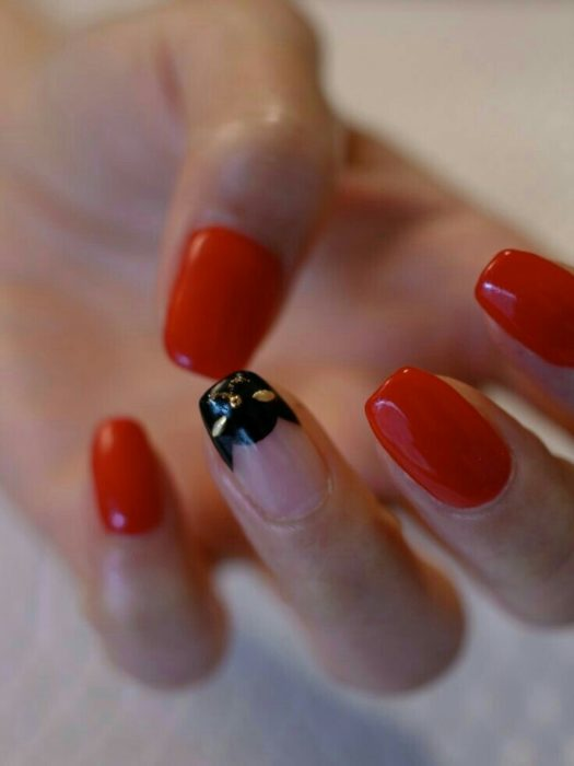 Cherry red tone manicure with black and gold cat silhouette decor