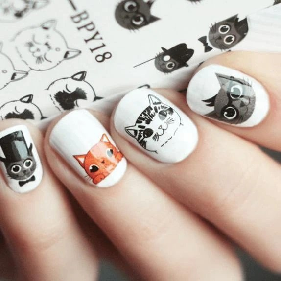 Manicure in white with stickers of cats in orange