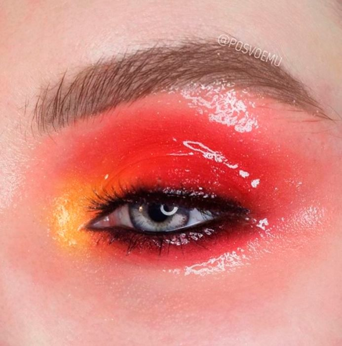 Red eye makeup with yellow gloss effect
