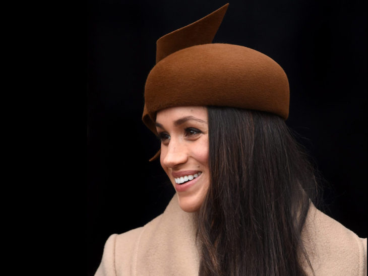 Meghan Markle usando un fascinator color café