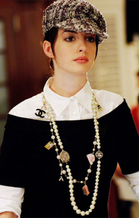 Scene from the movie El Diablo Dress up fashion. Andrea wearing a black sweater with a white blouse and a chanel necklace