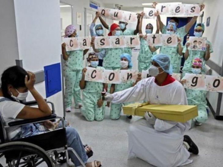 Personal médico sosteniendo letrero de propuesta de matrimonio