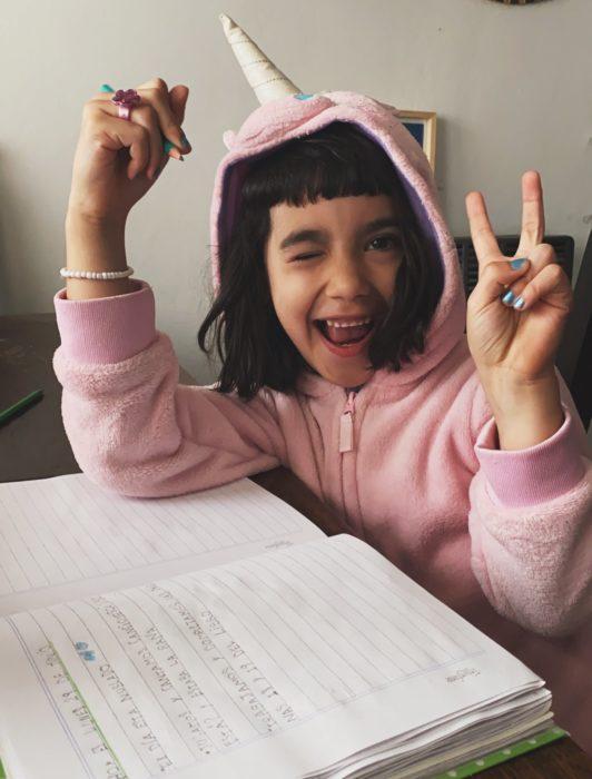 Niña llamada Angostina usando una sudadera de unicornio mientras está haciendo su tarea