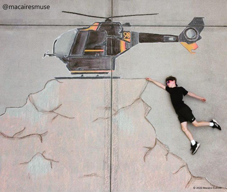 Dibujo de hecho con tiza de un helicoptero negro sobrevolando una montaña, niño recostado como si se sostuviera de la montaña