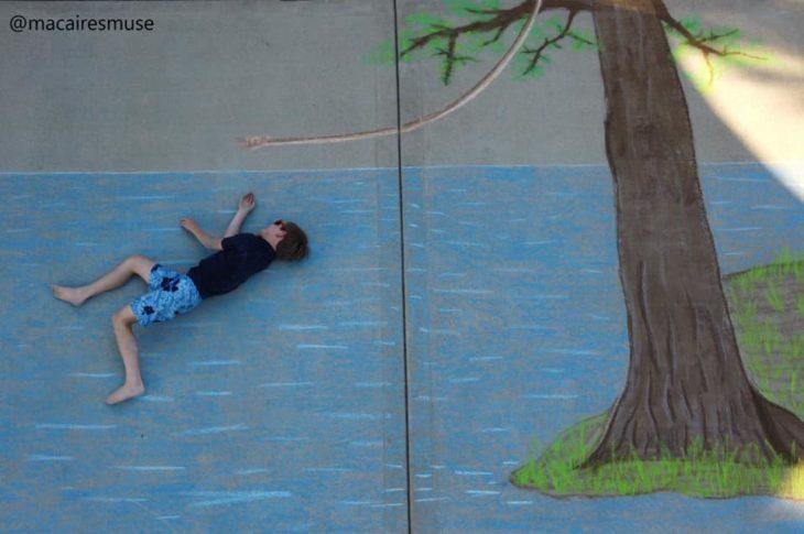 Dibujo de hecho con tiza de un niño lanzandose al agua después de sujetar una soga