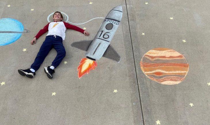 Dibujo de hecho con tiza de un niños sobrevolando el espacio