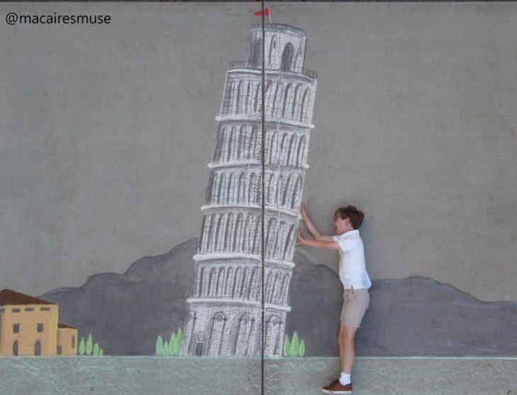 Dibujo de hecho con tiza de la torre eifeel en colores grises y verde con un niño que parece sostenerla