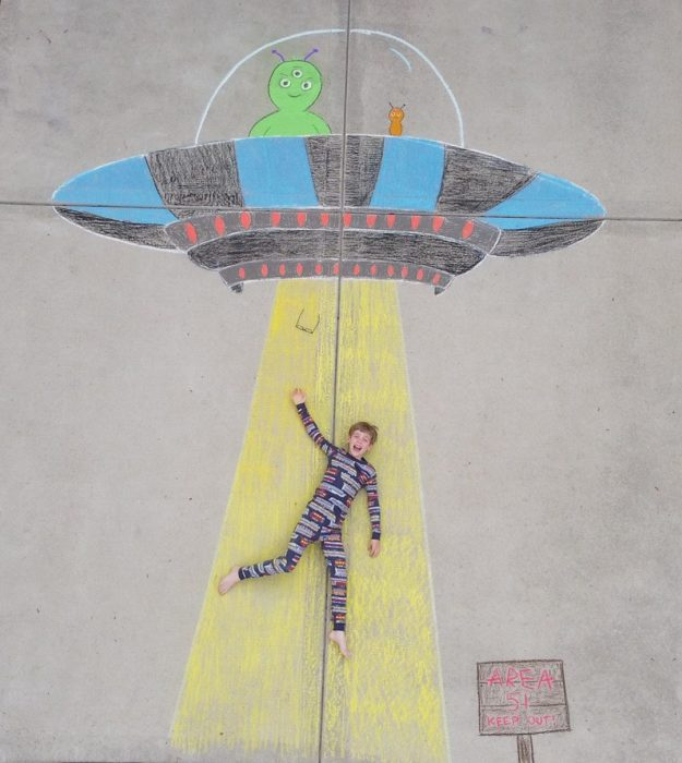 Dibujo de hecho con tiza de una abducción animada con aliens en color verde y un niño que parecer ser llevado por una luz amarilla
