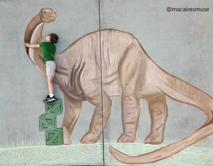 Dibujo de hecho con tiza de un niño saludando a un dinosaurio cuello largo