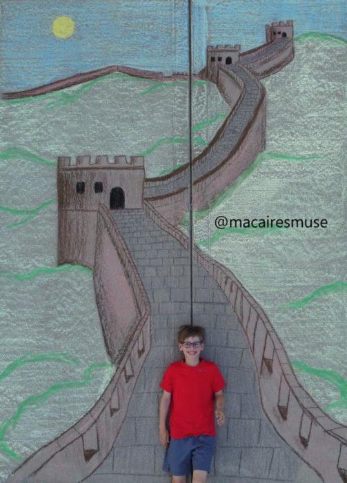 Dibujo de hecho con tiza de un niño caminando por la muralla china