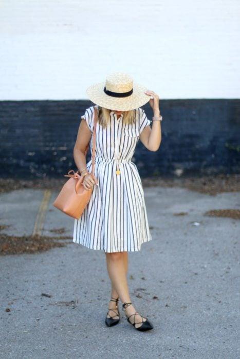 Chica usando vestido de rayas con sombrero y bucket bag color camel