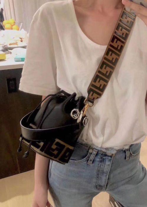 Chica usando mom jeans con camisa oversized y bucket bag pequeña color negra