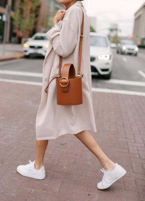 Chica usando tenis blancos, con un blazer largo y bucket bag color camel