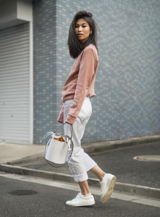 chica usando jeans capri blancos, con sudadera rosa, y bucket bag blanca