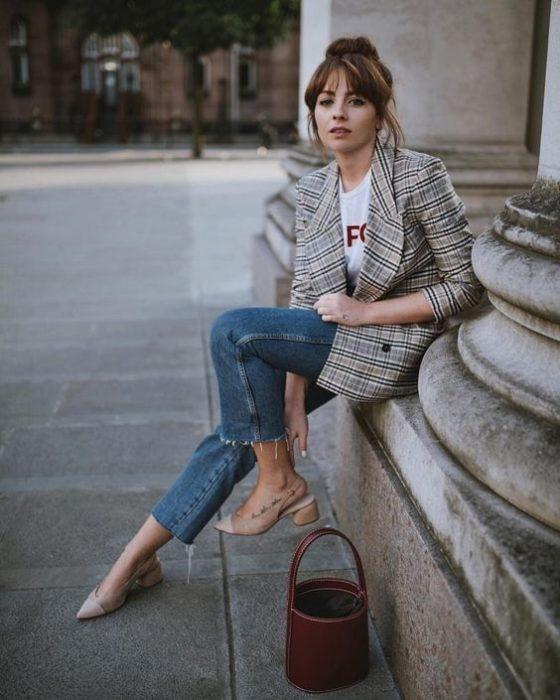 Chica usando jeans con playera blanca, blazer de estampado a cuadrosy bucket bag color café