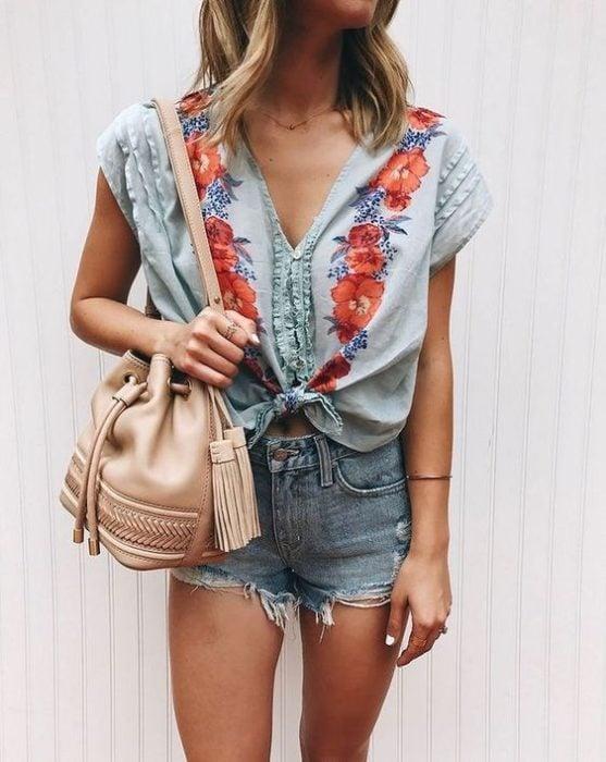 Chica usando shorts con blusa de bordado de flores y bucket bag color crema