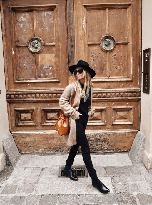 Chica usando outfit nego con abrigo color beige y bucket bag color camel