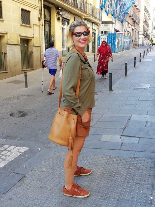 Chica usando bermudas con sudadera verde olivo con bucket bag color camel