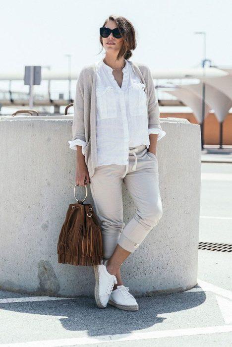 Chica usando conjunto de joggers y suéter color beige con camisa blanca y bucket bag de gamuza color café