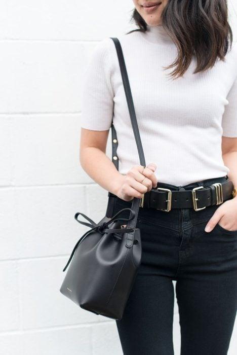 Chica usando top blanco con jeans negros y bucket bag color negro