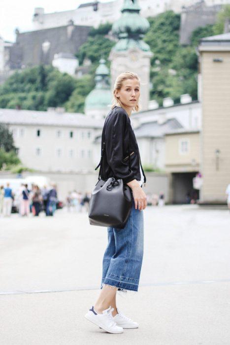 Chica usando tenis blancos, mom jeans, camisa negra y bucket bag color negro