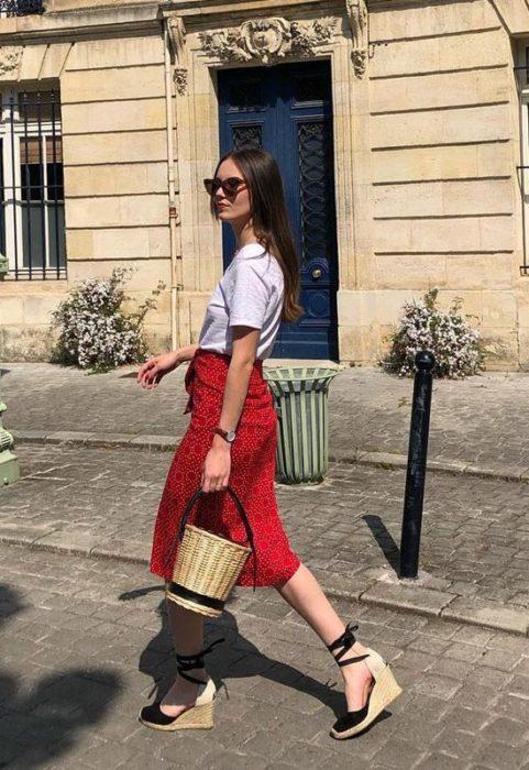 Chica usando falda roja, playera blanca, alpargatas negras y bucket bag de mimbre