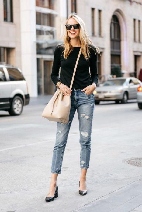 chica usando suéter negro con jeans rasgados tacones negros y bucket bag negra