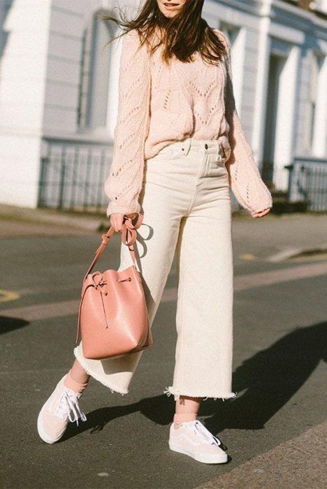 Chica usando jeans rectos con suéter rosa bebé y bucket bag color rosa