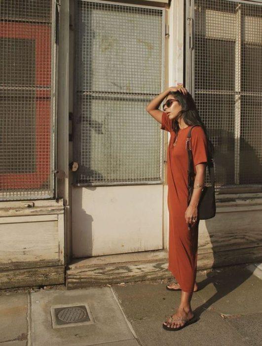 Mujer se toca el cabello y usa vestido naranja larga y flip flops