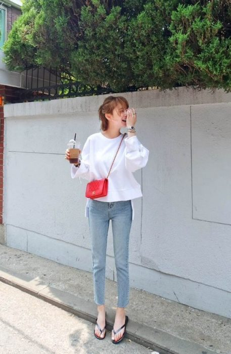 Short-haired girl holds a Coke and wears jenas, a white sweatshirt and flip flops