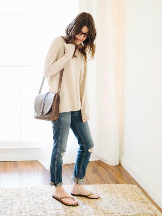 Girl in white long sweatshirt, brown bag, jeans and flip flops
