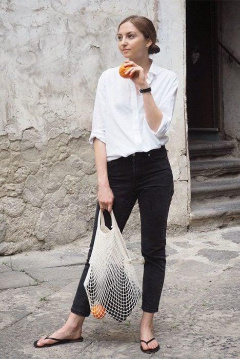 Girl in black pants, white blouse and flip flops