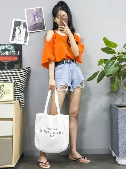 Asian girl in naanja loose blouse, denim shorts and flip flops