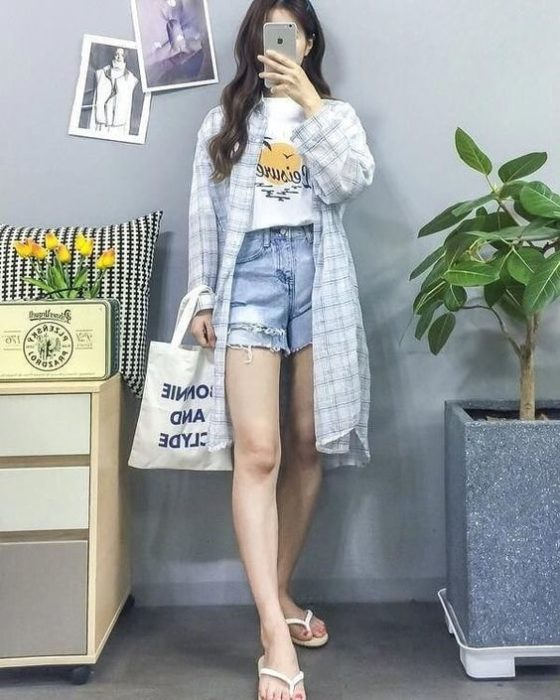 Girl taking selfie in front of the mirror with denim shorts, big shirt and white flip flops