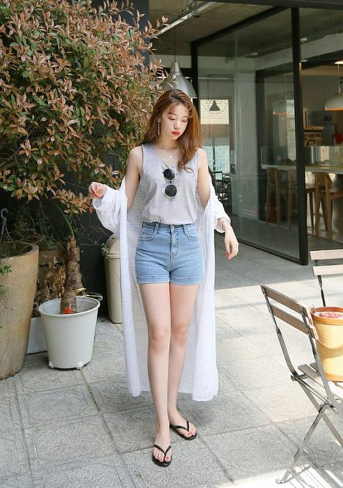 Girl walking down the street in denim shorts and gray blouse with black flip flips
