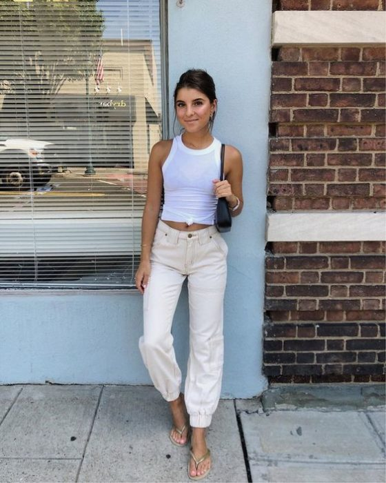 Girl posing on a wall wearing white blouse and beige pants and white flip flops