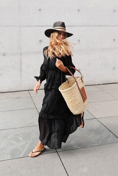 Blonde girl in long black dress walks down the street with flip flops