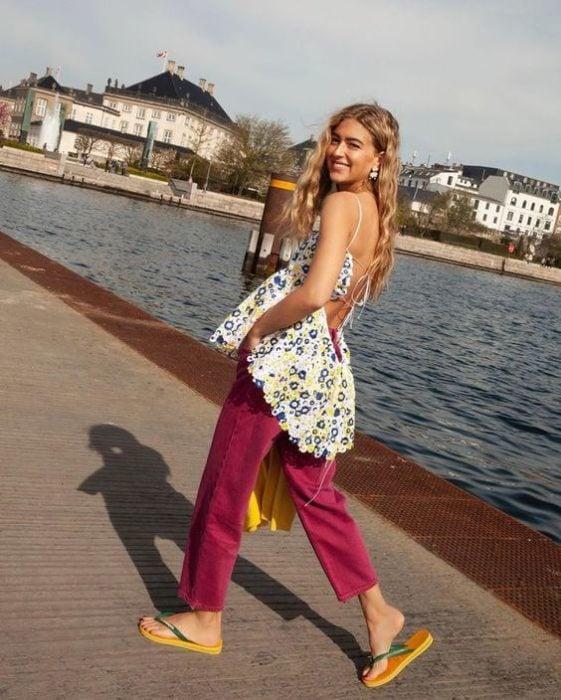 Blonde girl walking on a lake in pink pants and flip flops