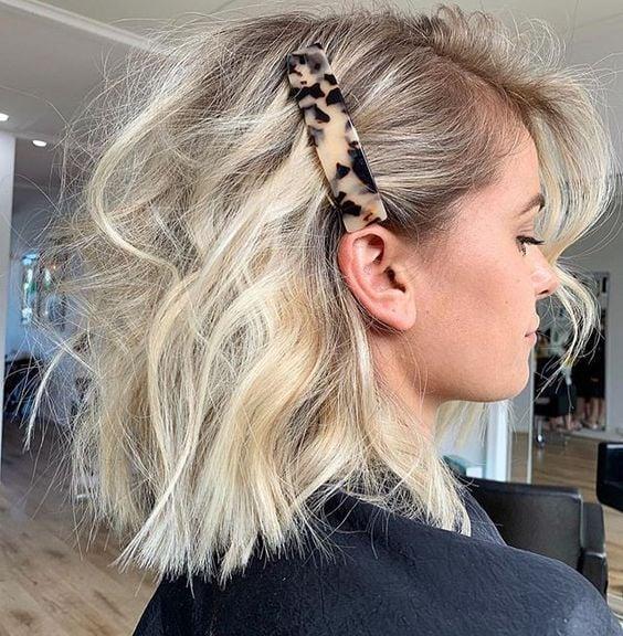 Chica rubia de cabello corto con broche grande en el costado