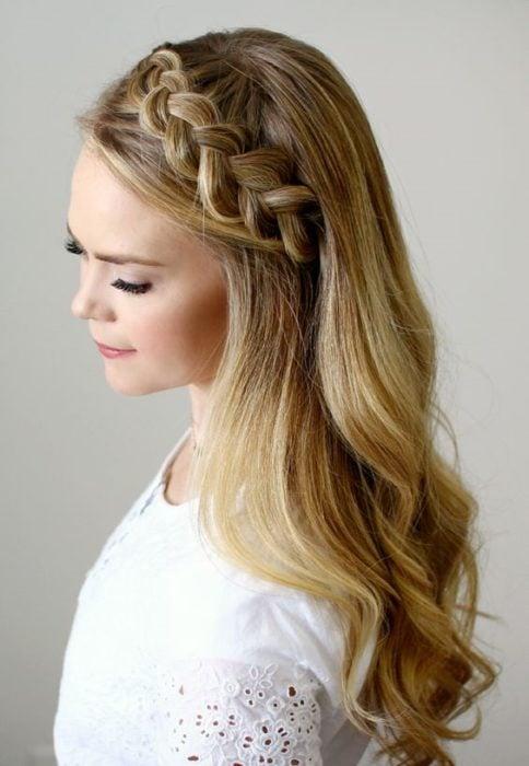 Chica rubia de cabello suelto con trenza alemana en diagonal