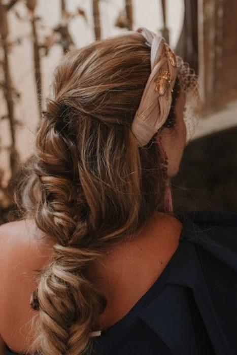 Chica con recogido elegante despeinado con diadema beige con detalles dorados