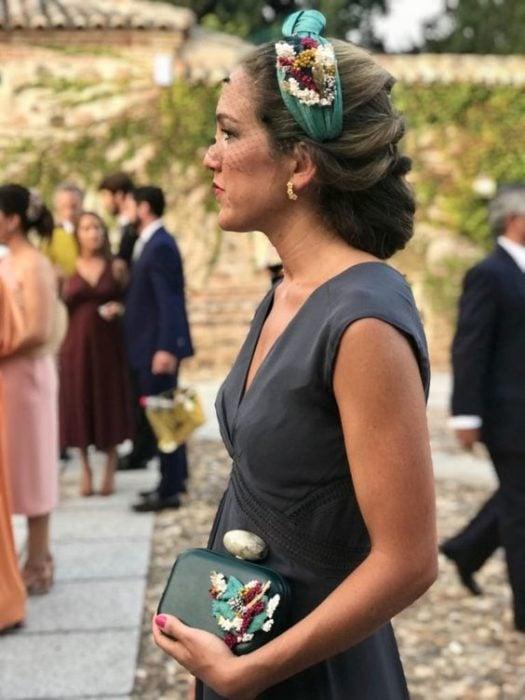 Invitada de boda con recogido elegante y diadema color verde con flores