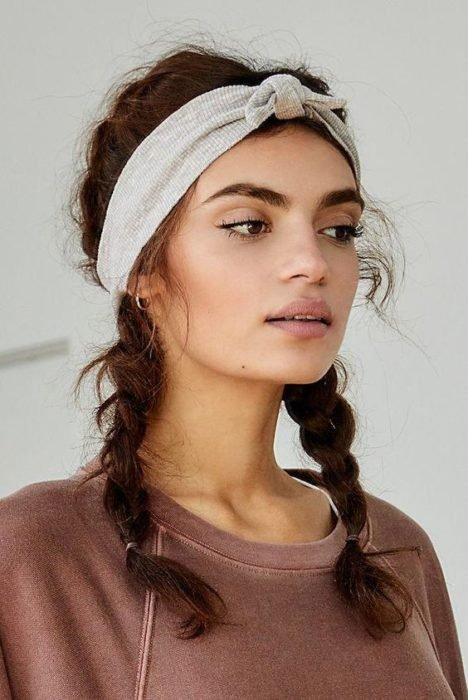 Chica morena de cabello rizado con trenzas y diadema gris